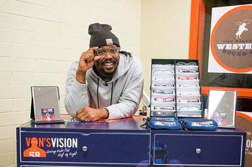 Von Miller leaning on a table for Von's Vision