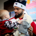 Kyle Van Noy giving a gift to a child