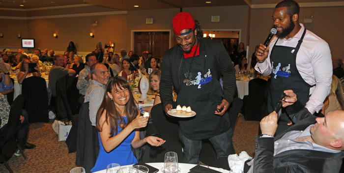 Players serve cupcakes to attendees